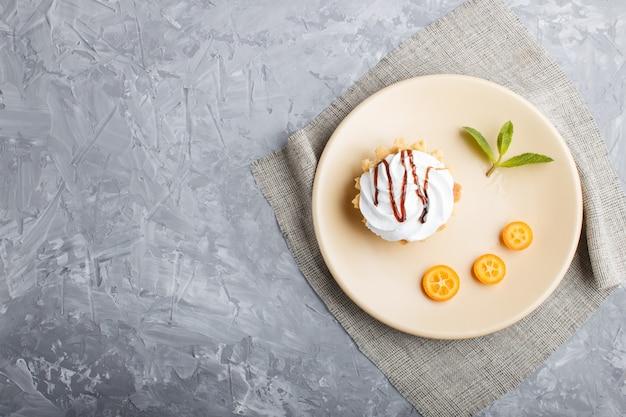 Gâteau à la crème d'œuf fouettée sur une plaque brun clair avec du kumquat et des feuilles de menthe Photo Premium