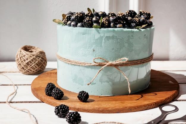 Gâteau crème turquoise aux bleuets et aux mûres, nature morte Photo Premium