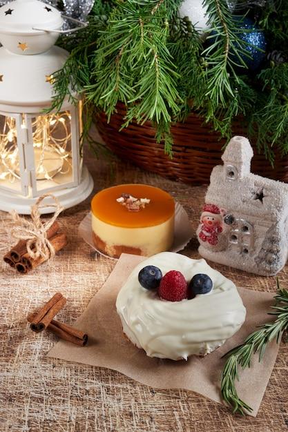 Un Gâteau Décoré De Mûres Et De Framboises Sur Une Table De Noël Avec Une Lampe De Poche Et Une Branche D'épinette. Cadre Vertical Photo Premium