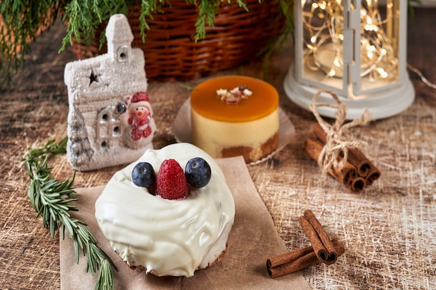 Un Gâteau Décoré De Mûres Et De Framboises Sur Une Table De Noël Avec Une Lampe De Poche Et Une Branche D'épinette. Nouvel An Photo Premium