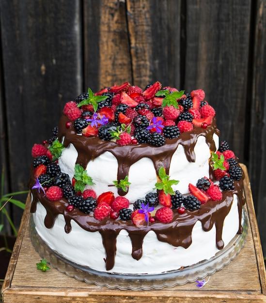 Gâteau à deux niveaux avec des fruits et des fleurs. dessert. forêt noire Photo Premium