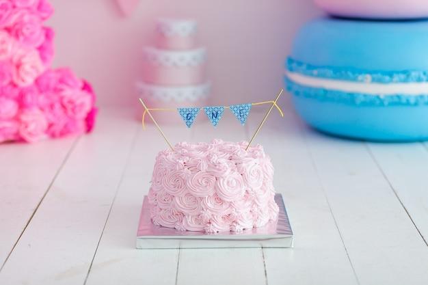 Gâteau festif rose crème à l'ombre rose sur gros macaron bleu. smash de gâteau de première année. Photo gratuit