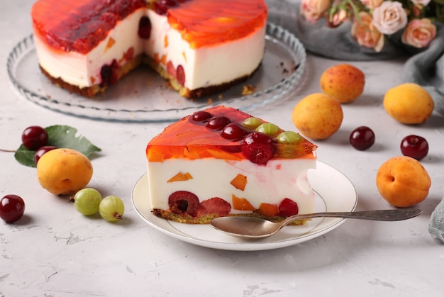 Gâteau à La Gelée Fait Maison Avec Des Baies Sur Fond Gris Et Tranche De Gâteau Sur Une Assiette Photo Premium
