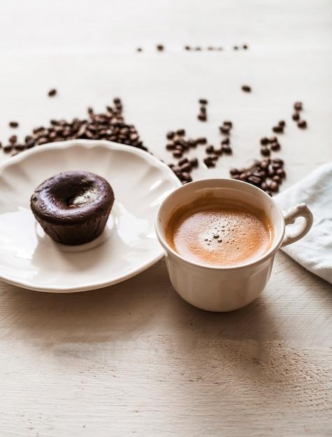 Gâteau de lave au chocolat sur une assiette avec une tasse à café et des grains de café torréfiés Photo gratuit