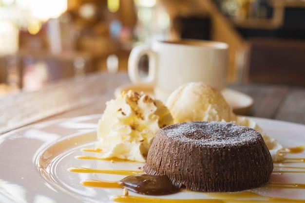Gâteau de lave au chocolat dans une assiette blanche avec une tasse de café dans un café Photo gratuit