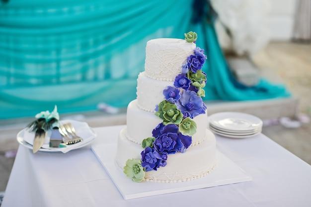 Gâteau de mariage blanc décoré de fleurs bleues Photo Premium