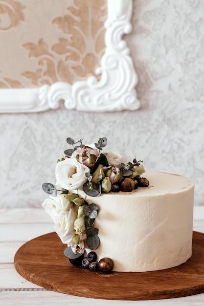 Gâteau De Mariage Blanc Décoré De Fleurs D'eustoma Et D'eucalyptus. Place Pour Le Texte. Photo Premium