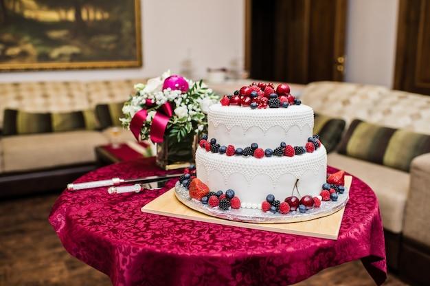 Gâteau de mariage classique avec framboises, fraises, mûres et myrtilles. Photo Premium