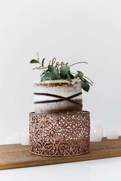 Un gâteau de mariage décoratif avec un gâteau de mariage sur une table en bois Photo gratuit