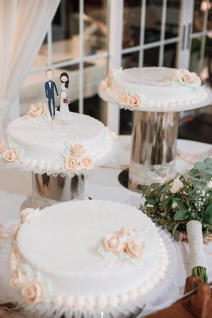 Gâteau de mariage avec des figurines drôles d'époux et épouse. Photo Premium