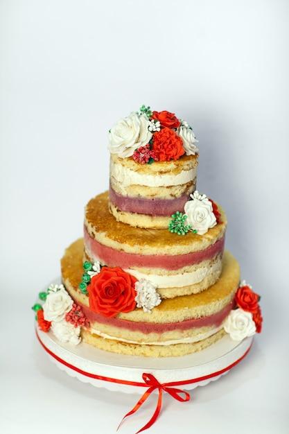 Gâteau de mariage. gâteau à la main nue rustique, décorée avec des roses. Photo Premium