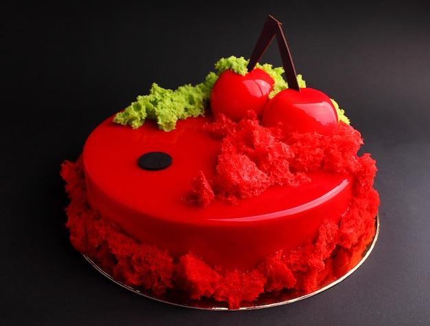 Gâteau à la mousse de baies dans le glaçage rouge miroir orné d'un biscuit moléculaire. sur le fond noir Photo Premium