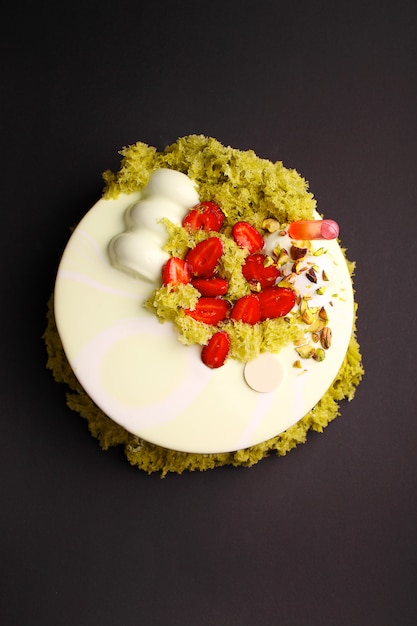 Gâteau à la mousse de baies avec glaçure miroir. décoré de fraises et de biscuits moléculaires. sur le fond noir Photo Premium