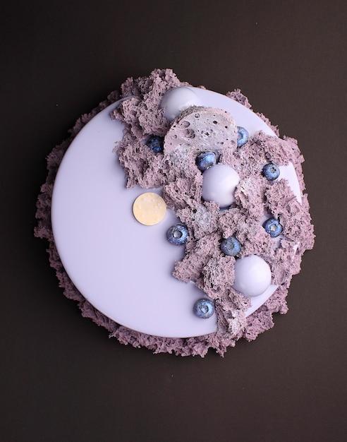 Gâteau à la mousse de mûre dans le glaçage miroir décoré avec un biscuit moléculaire. sur le fond noir Photo Premium