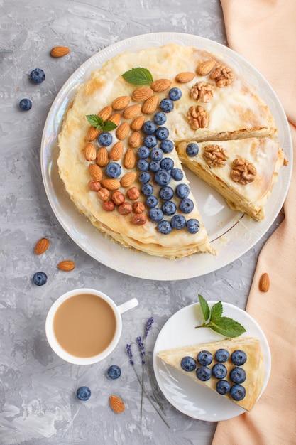 Gâteau napoléon fait maison en couches avec de la crème de lait. décoré de myrtilles, amandes, noix, noisettes, menthe Photo Premium