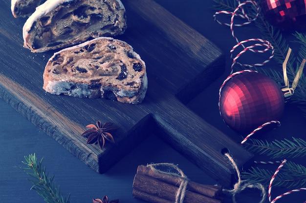 Gâteau de noël traditionnel avec des raisins secs et des noix avec des branches d'arbres et des jouets Photo Premium