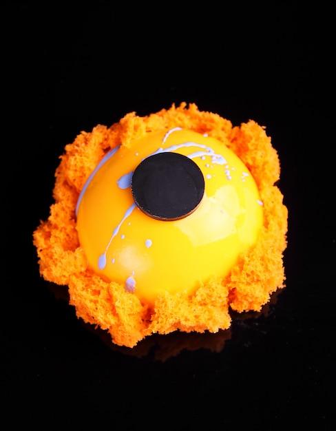 Le gâteau orange à la glaçure miroir est décoré avec un biscuit moléculaire sur fond noir Photo Premium