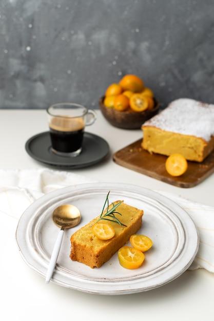 Gâteau orange servi décoré de kumquats et de romarin frais, planche à découper en bois, café expresso Photo Premium