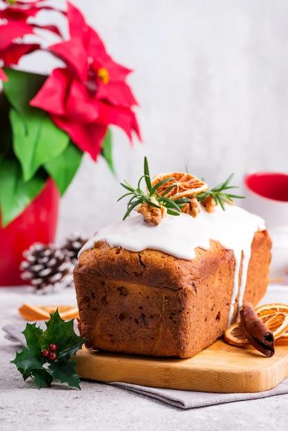 Gâteau de pain aux fruits saupoudré de glaçage, noix et orange séchée sur pierre. poinsettia sur les vacances de noël et d'hiver Photo Premium