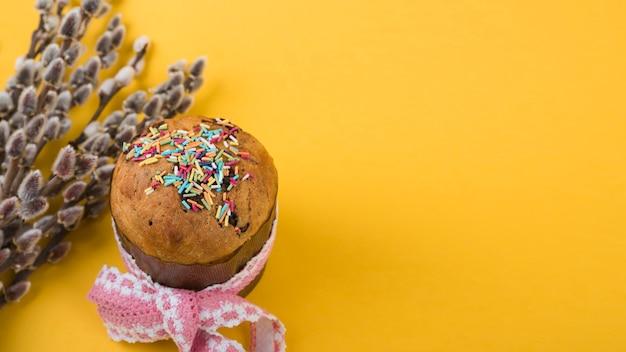 Gâteau de pâques avec des branches de saule sur une table jaune Photo gratuit