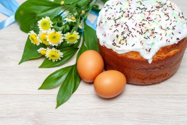 Gâteau de pâques et fleurs d'oeufs colorés fleurs jaunes sur fond Photo Premium