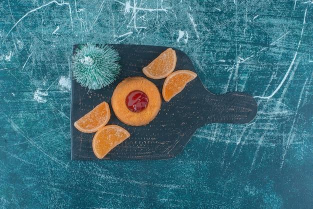 Gâteau Rempli De Gelée, Marmelades Et Une Figurine D'arbre Sur Un Tableau Noir Sur Fond Bleu. Photo De Haute Qualité Photo gratuit