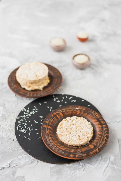 Gâteau de riz soufflé rond et riz sur fond texturé Photo gratuit