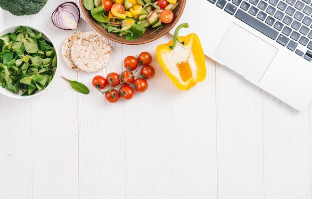 Gâteau de riz soufflé; salade de légumes et salade de maïs frais laisse avec un ordinateur portable ouvert sur le bureau blanc Photo gratuit