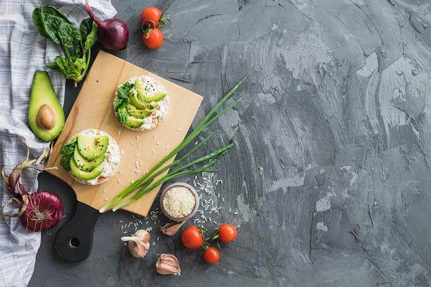 Gâteau de riz avec des tranches d'avocat sur une planche à découper avec les ingrédients crus sur le comptoir de ciment Photo gratuit