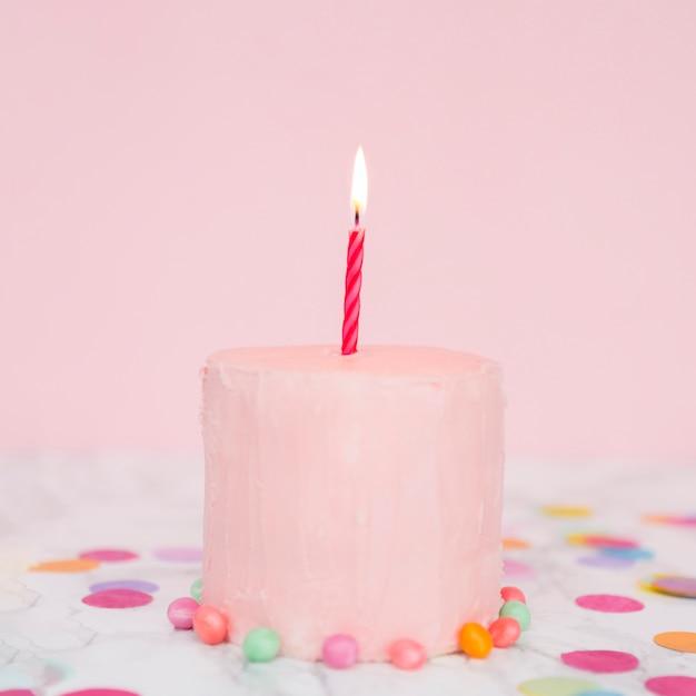 Gâteau rose avec une bougie allumée Photo gratuit