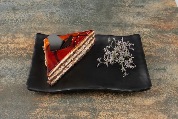 Gâteau Savoureux Sur Assiette Avec Fleur Sur Surface En Marbre. Photo gratuit