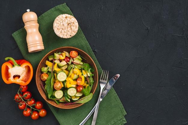 Gâteau soufflé au riz; salade de légumes et poivrières sur serviette de table sur fond de béton texturé noir Photo gratuit