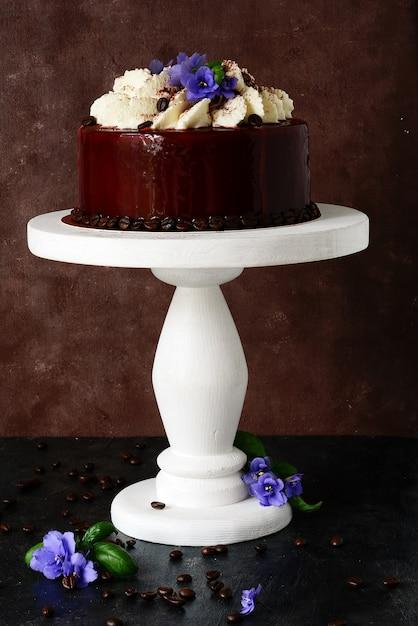 Gâteau Tiramisu En Glaçage Au Chocolat à La Crème De Mascarpone Et Décoré De Grains De Café Et De Violettes Photo Premium