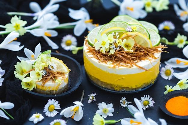 Gâteau Végétalien Cru Au Citron Et Citron Vert Sur Une Surface Noire Recouverte De Petites Fleurs De Marguerite Photo gratuit