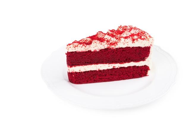 Gâteau de velours rouge coupé en morceaux sur une plaque blanche sur fond blanc Photo Premium