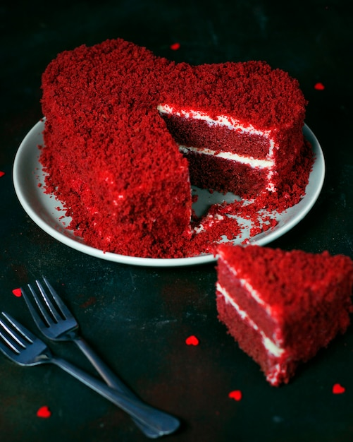 Gâteau velours rouge en forme de coeur sur noir Photo gratuit
