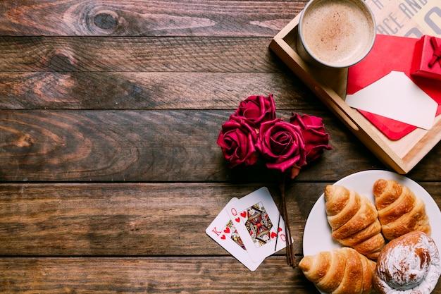Gâteaux sur assiette près de fleurs et cartes à jouer près de tasse de boisson et lettre à bord Photo gratuit