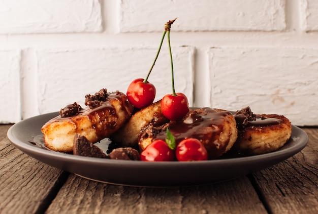 Gâteaux au fromage crêpes aux cerises et au chocolat sur un fond noir d'une table en béton et un mur de briques blanches. Photo Premium