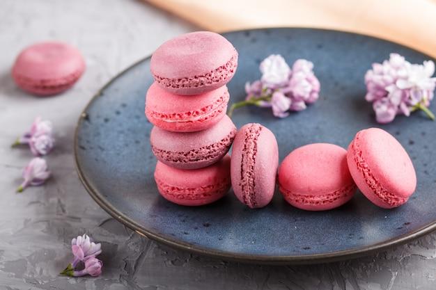 Gâteaux macaron ou macaron violet et rose sur une plaque en céramique bleue sur fond de béton gris. Photo Premium