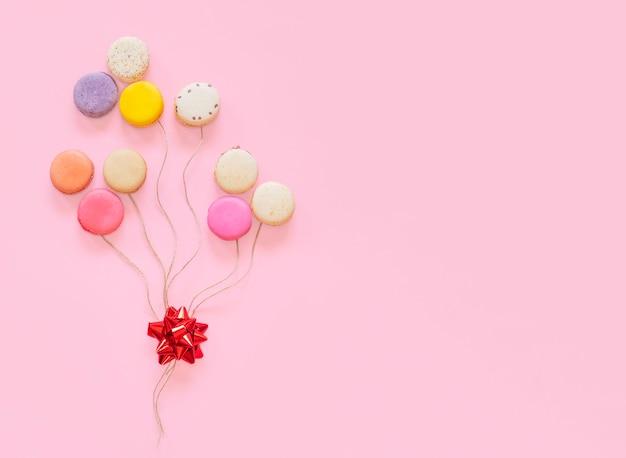 Gâteaux macarons colorés français sous forme de ballons isolés sur fond rose. Photo Premium