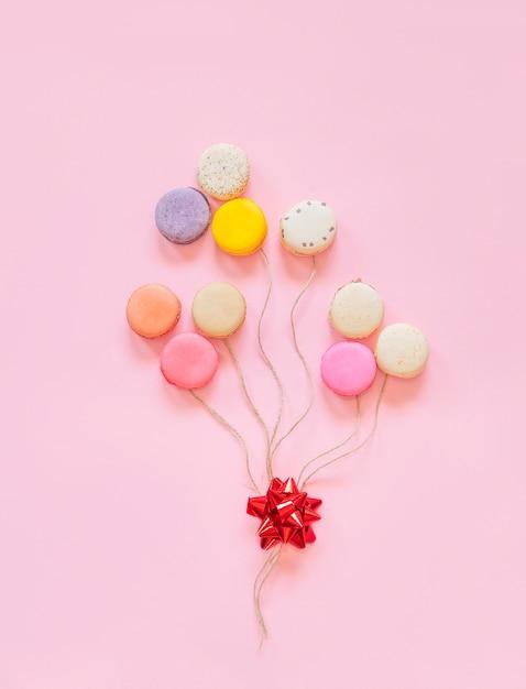 Gâteaux macarons français colorés. petits biscuits sucrés. dessert. lay plat de macarons sous forme de ballons. joyeux anniversaire et concept minimal créatif de la saint-valentin. Photo Premium