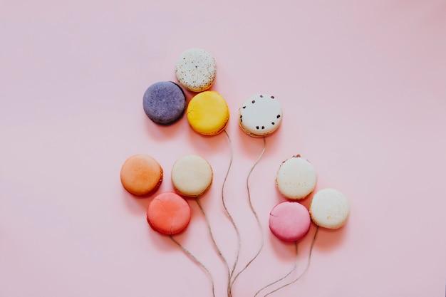 Gâteaux macarons français colorés. petits biscuits sucrés isolés. dessert. lay plat de macarons sous forme de ballons. joyeux bithday et valentin concept créatif minimal. Photo Premium