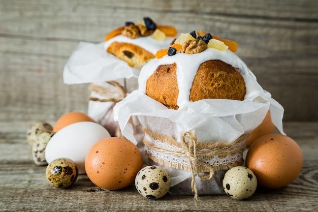 Gâteaux de pâques avec des oeufs, fond de bois rustique Photo Premium