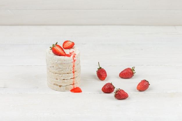 Gâteaux De Riz Blanc Gros Plan Avec Des Fraises Sur La Surface De La Planche De Bois Blanc. Horizontal Photo gratuit