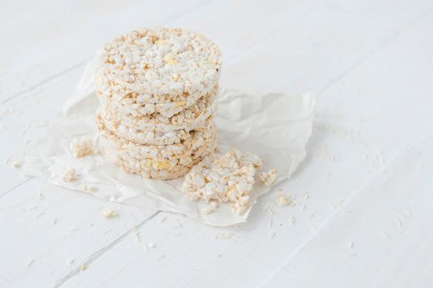 Gâteaux de riz soufflé cassé et rond sur une table en bois blanc Photo gratuit