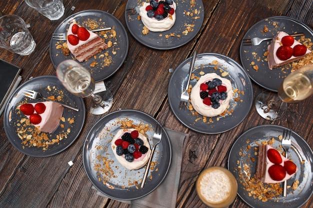 Gâteaux Sucrés Avec Des Baies D'été Sur Une Table En Bois. Fête, Table Sucrée. Desserts D'été Au Restaurant. Photo Premium