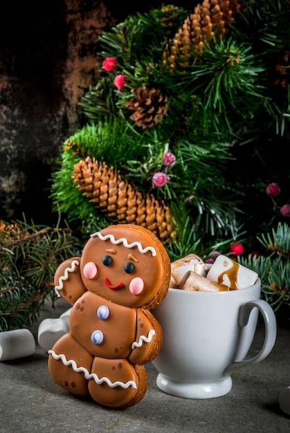 Gâterie de noël traditionnelle. chocolat chaud avec guimauve, biscuit de pain d'épice, branches de sapin et fond de décorations de noël Photo Premium