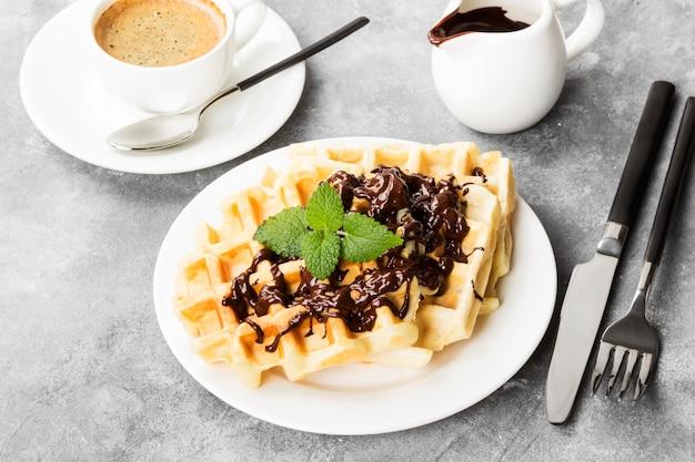 Gaufres sur assiette blanche au chocolat et à la menthe, café, saucière au chocolat Photo Premium