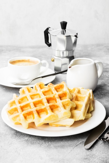 Gaufres sur assiette blanche, café et saucière au chocolat Photo Premium