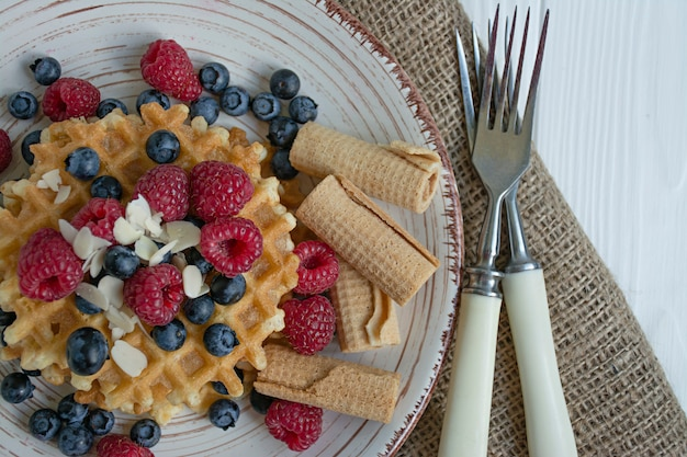 Gaufres aux fruits frais pour le petit déjeuner. gaufres ensoleillées. fond en bois blanc Photo Premium